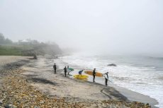 Several men in wet suits with surfboards on a rocky Martha's Vineyard beach