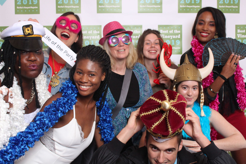 Colorfully costumed winners pose in a photo booth at the Best of the Vineyard party.