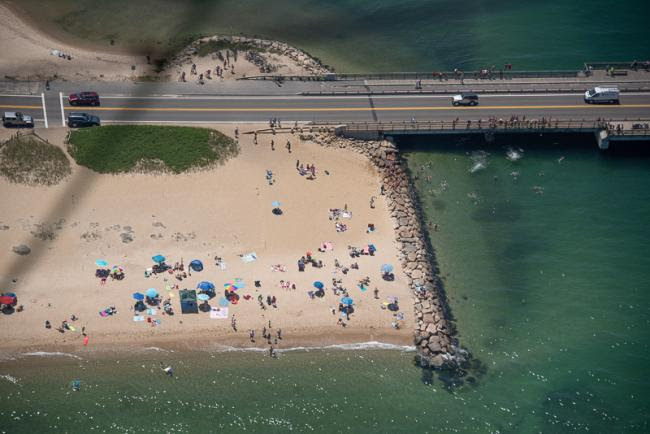 Aerial view of State Beach each and bridge with jumpers splashing into the water