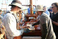 Oyster farmers shuck shellfish aboard a boat.