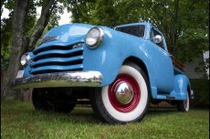a close-up photo of the front of a baby-blue vintage pickup truck with white sidewall tires and red rims