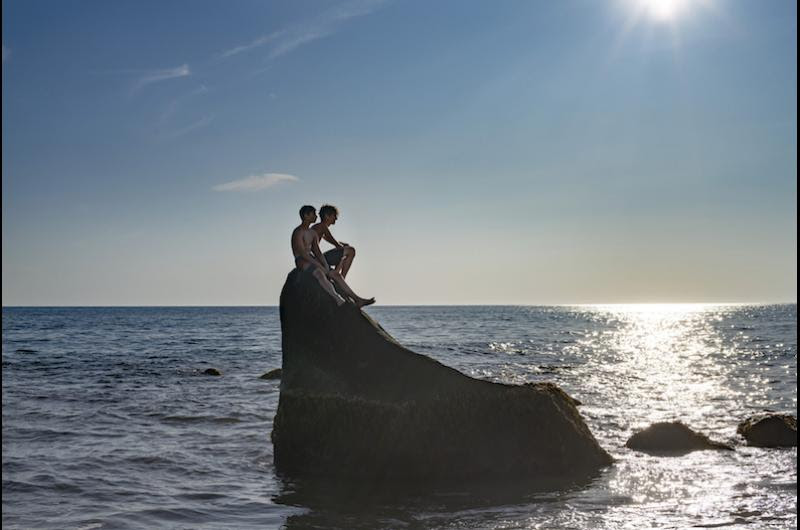 Two young swimmers sit atop a boulder in the water off the Gay Head Cliffs