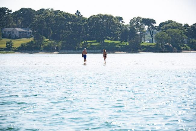 Two people on stand-up paddle boards on a pond