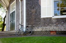 A bicycle leans against a shingled wall. Photo by Timothy johnson